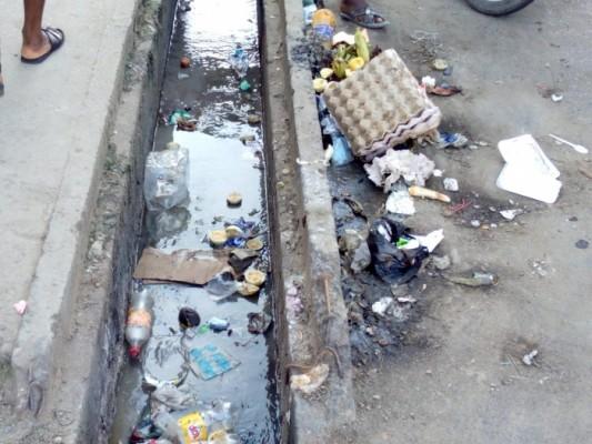 Bordure de route et caniveau dans un quartier de Douala encombré de saleté
